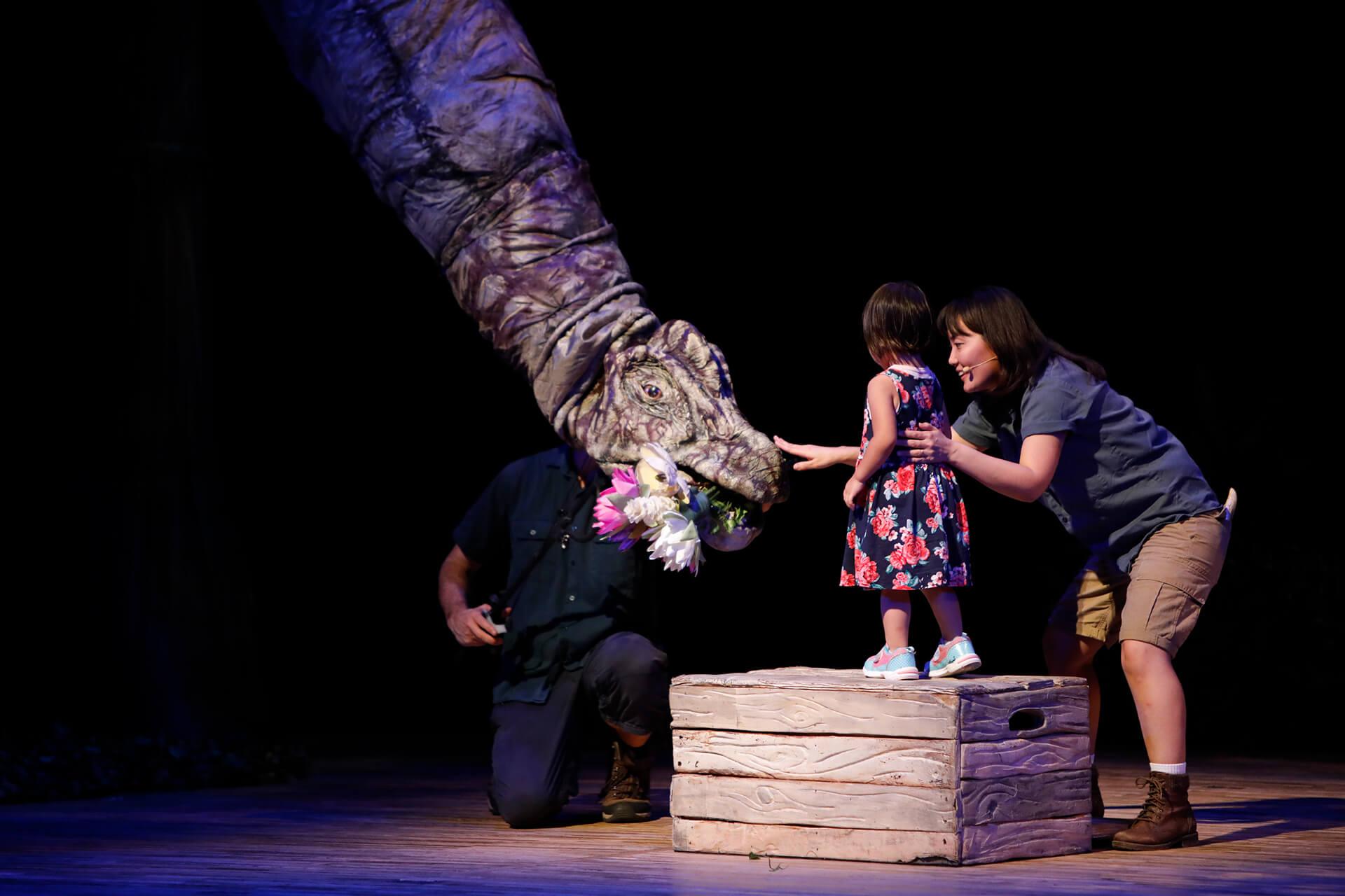 この写真は首長恐竜と戯れる子供です