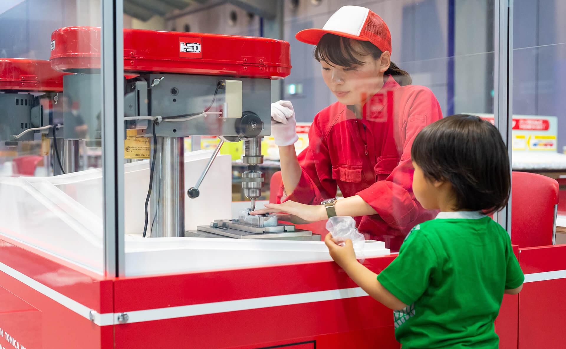 この写真はトミカ博でのトミカ組み立て工場を眺める子供の様子です