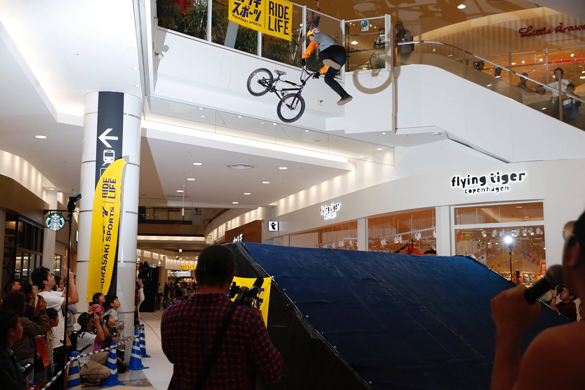 この写真は越谷イオンレイクタウンにて、 スケートボード&BMXスペシャルパフォーマンスショーのパフォーマンスの様子。バイクが空を舞っている様子です