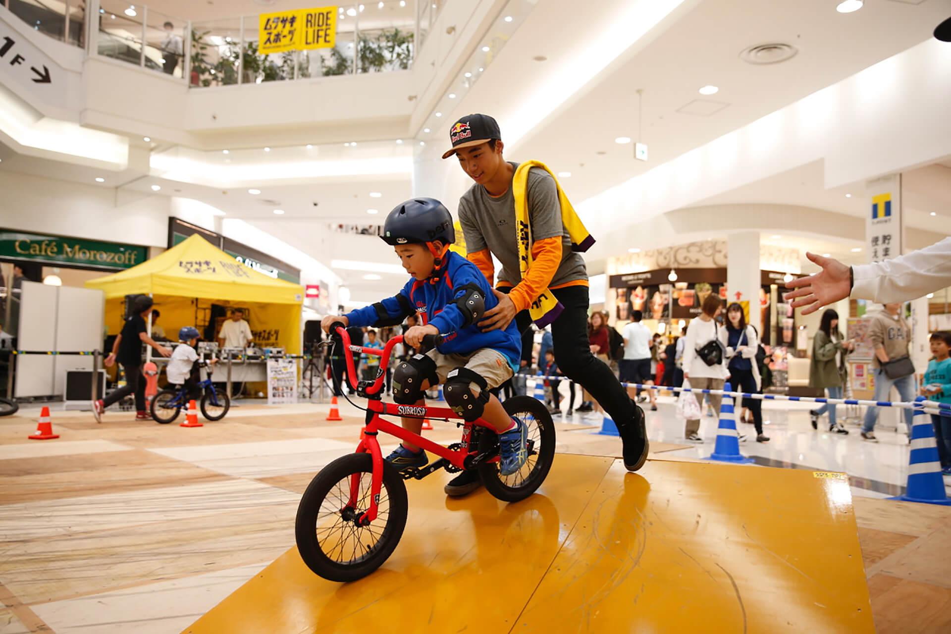 この写真は越谷イオンレイクタウンにて、 スケートボード&BMXスペシャルパフォーマンスショーのパフォーマンスの様子。ちびっこが体験する様子です