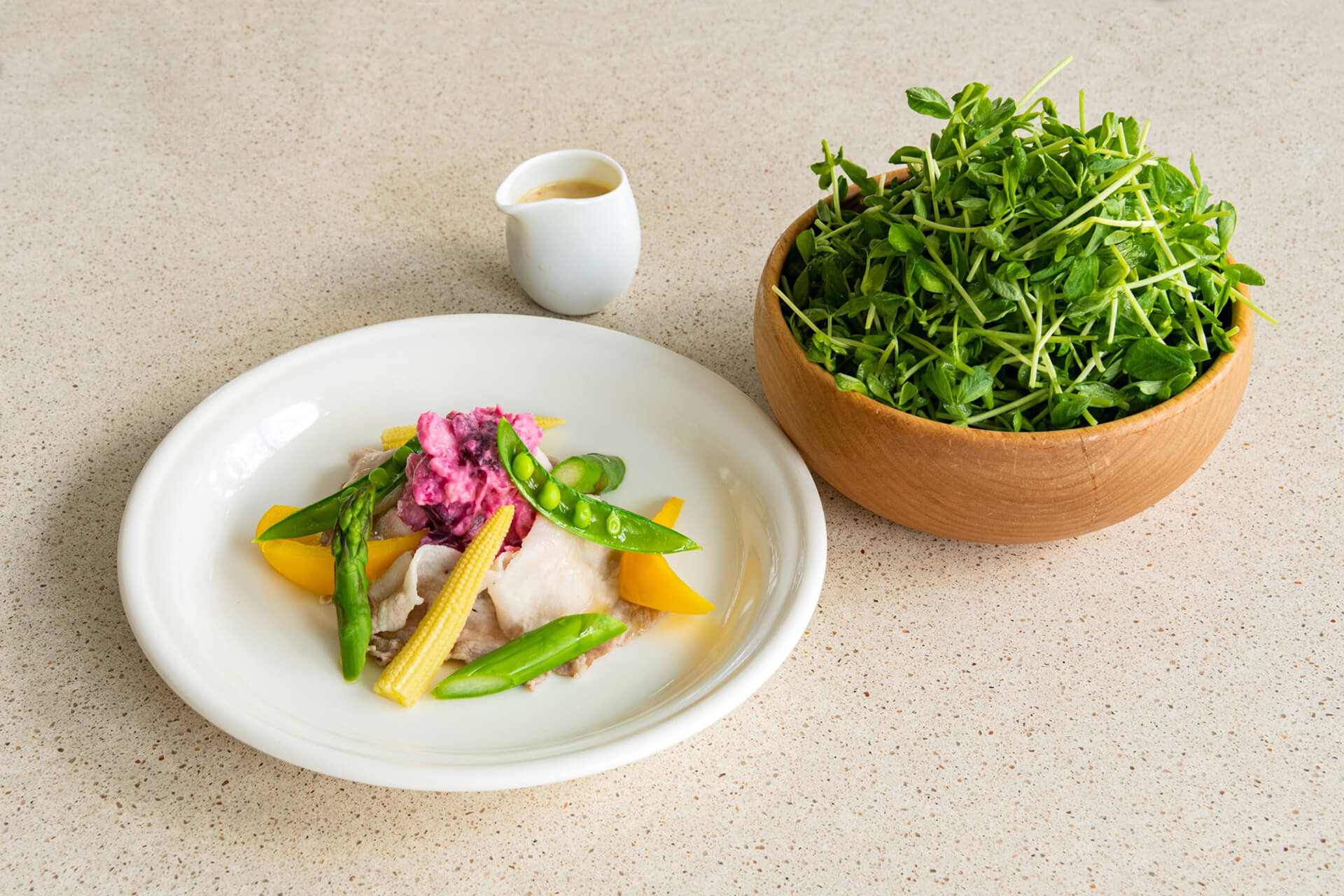 この写真は「豆苗カフェ」で販売する、豚しゃぶと彩り野菜の豆苗サラダ ~豆乳味噌ドレッシング~ です