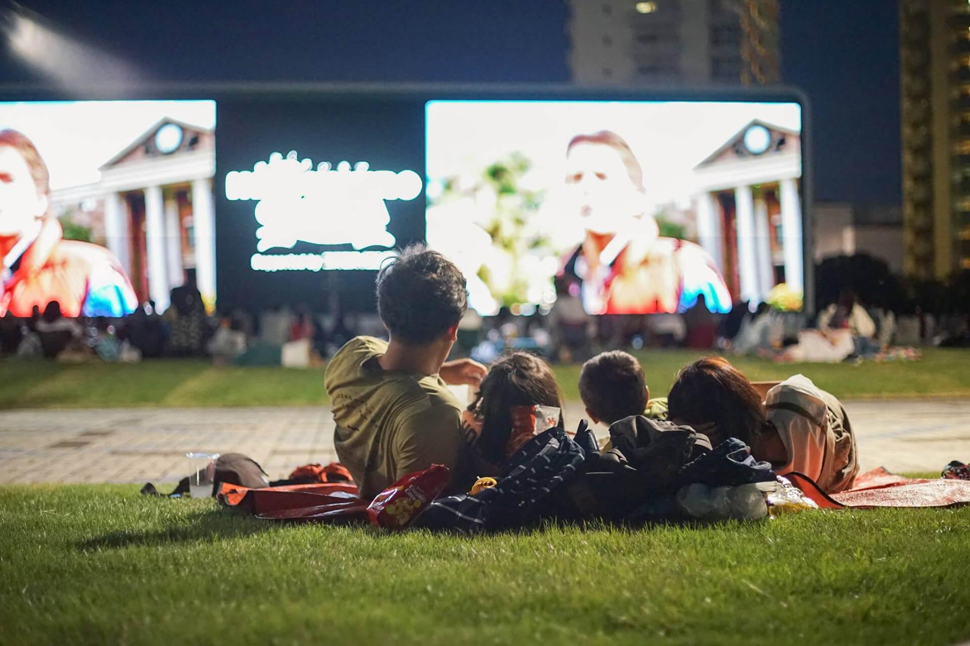 この写真は、ねぶくろシネマの告知バーナー。野外で映画を楽しむ様子です