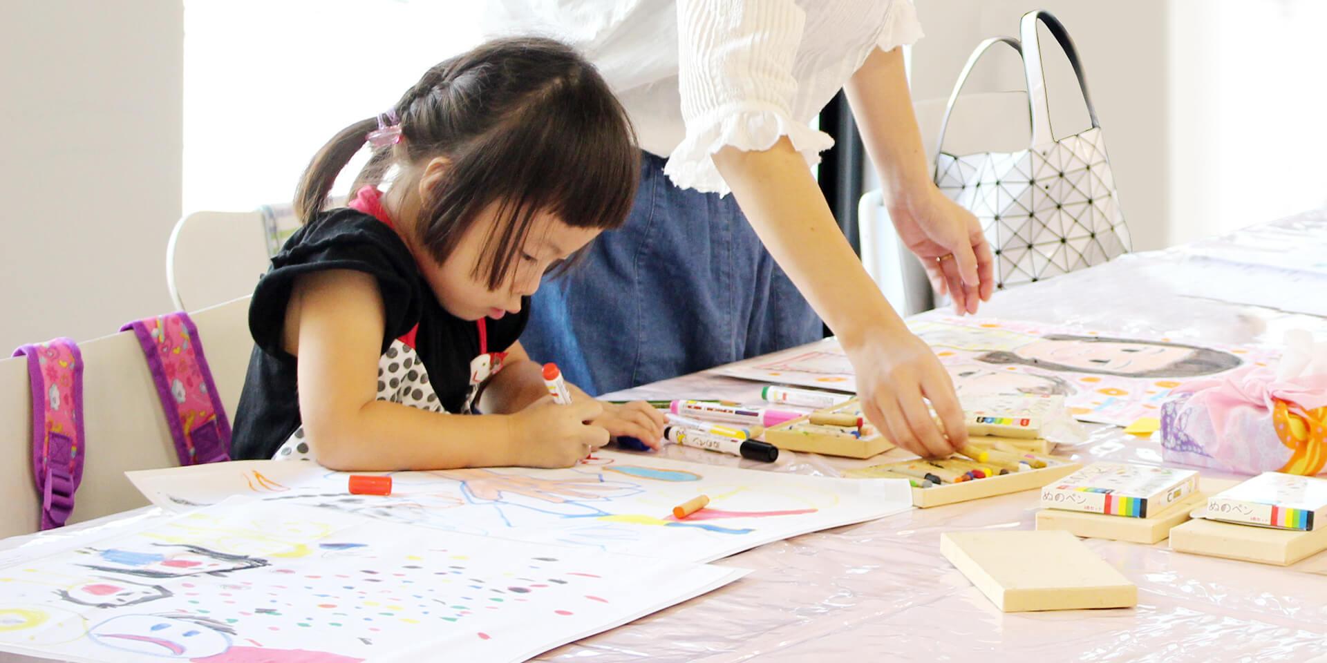 この写真は、なつやすみ 親子でたのしくハンカチーフに絵をかこうに参加し、製作している子供の様子