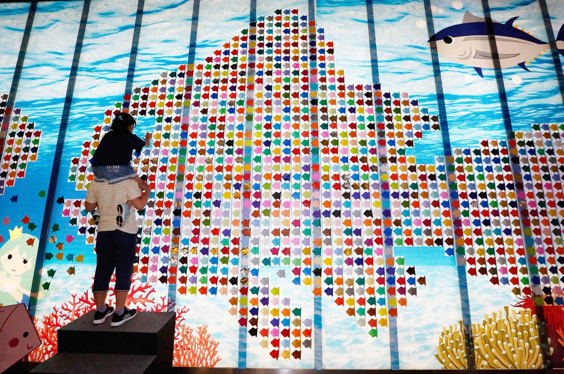 この写真は、丸の内キッズジャンボリーの折り紙でラガーシャツを作って、 ギネス世界記録™に挑戦の様子