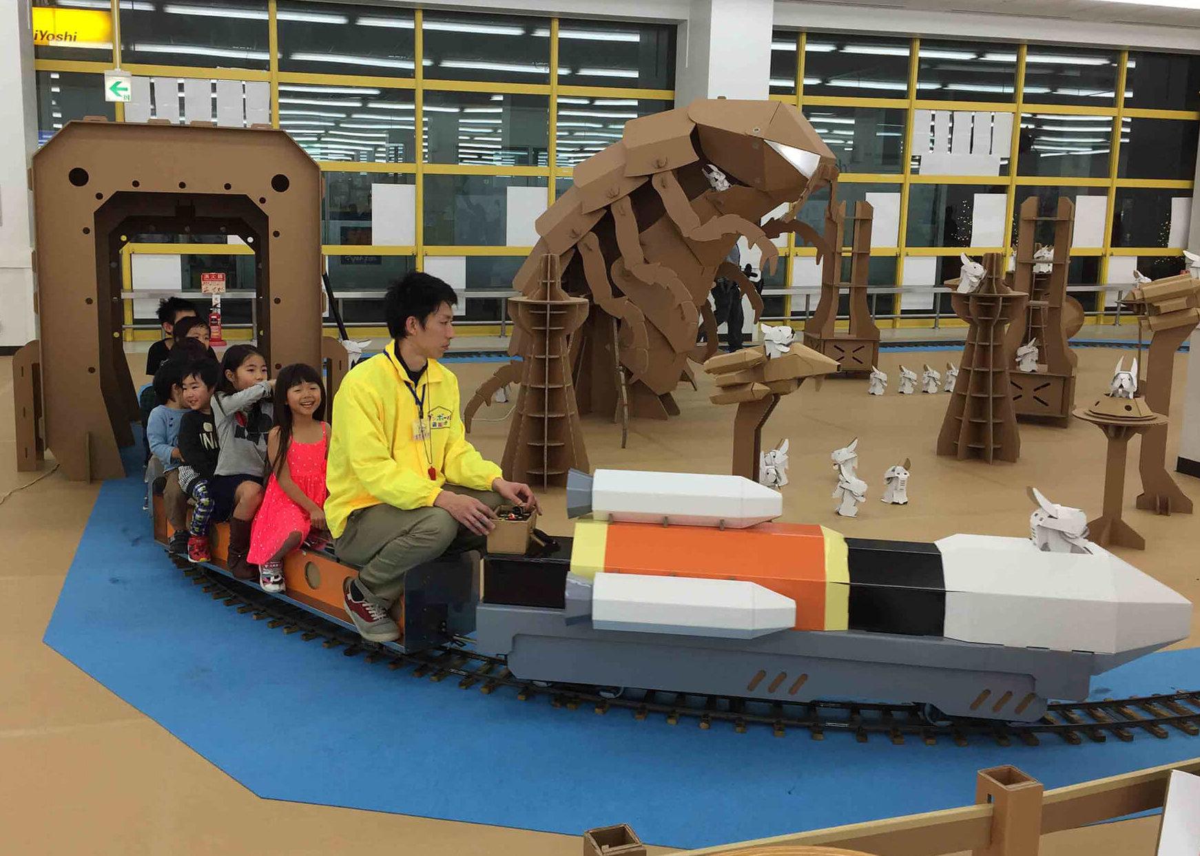 この写真はダンボール宇宙遊園地で、ロケット電車で遊ぶ子供達