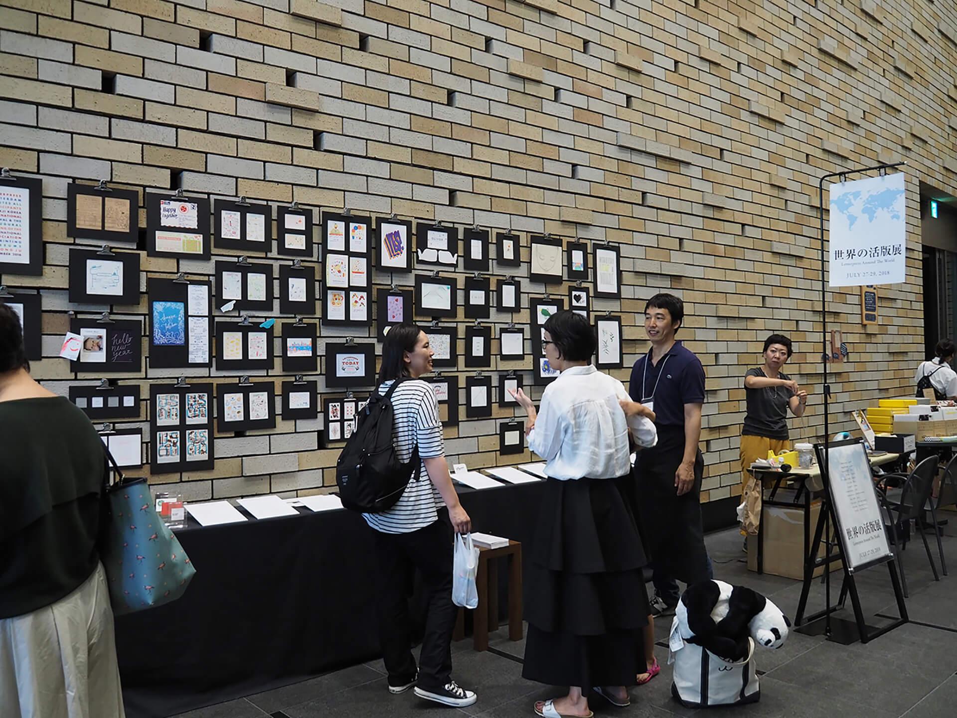 この写真は活版TOKYO2019の世界の展示展の様子。スタッフが説明しています