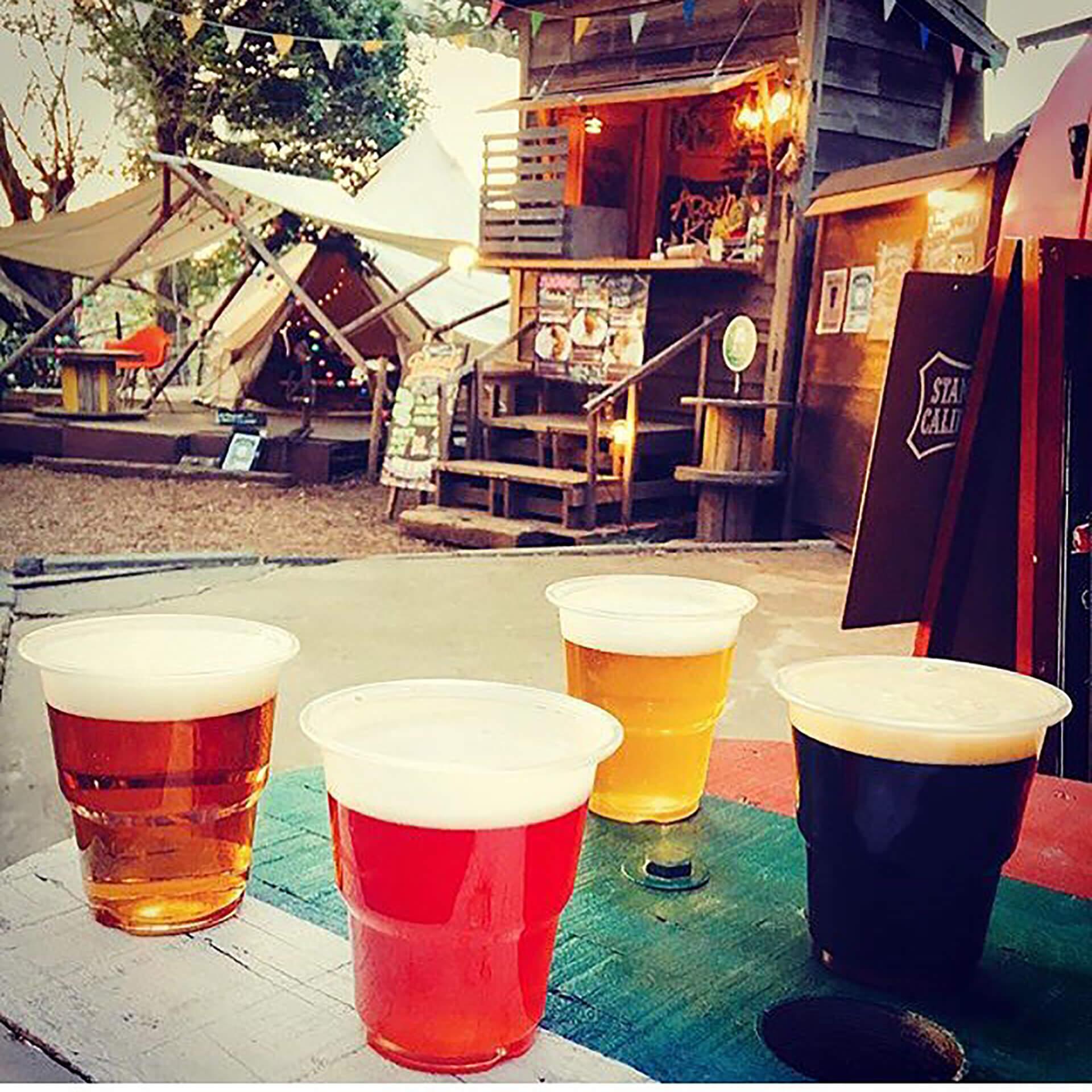 この写真はコムナdeビアガーデンで販売されるビールの雰囲気写真。会場をからめて4つのビールを撮影しています