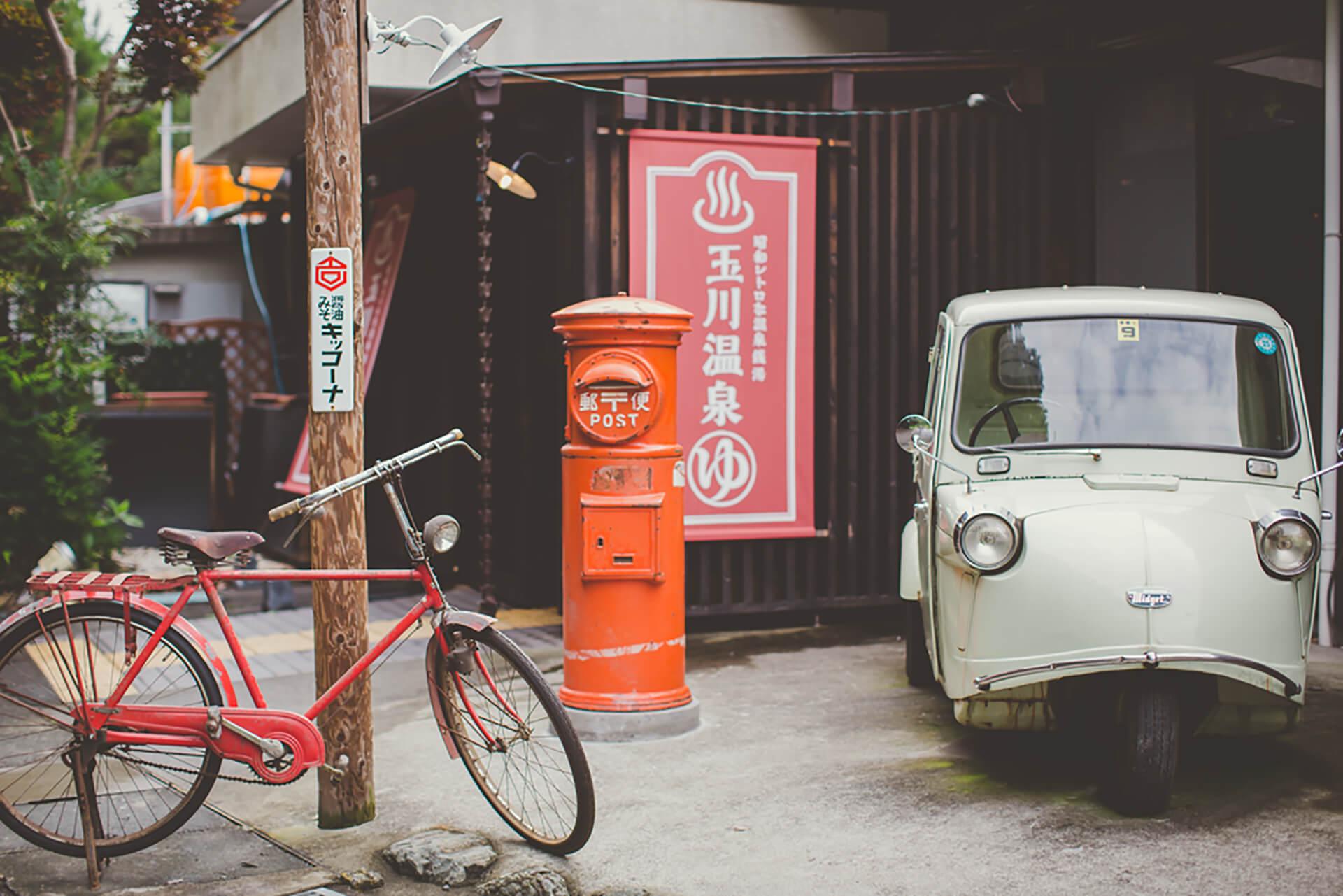 玉川温泉のメインビジュアル・昭和のクルマやポスト、自転車が並んでいます