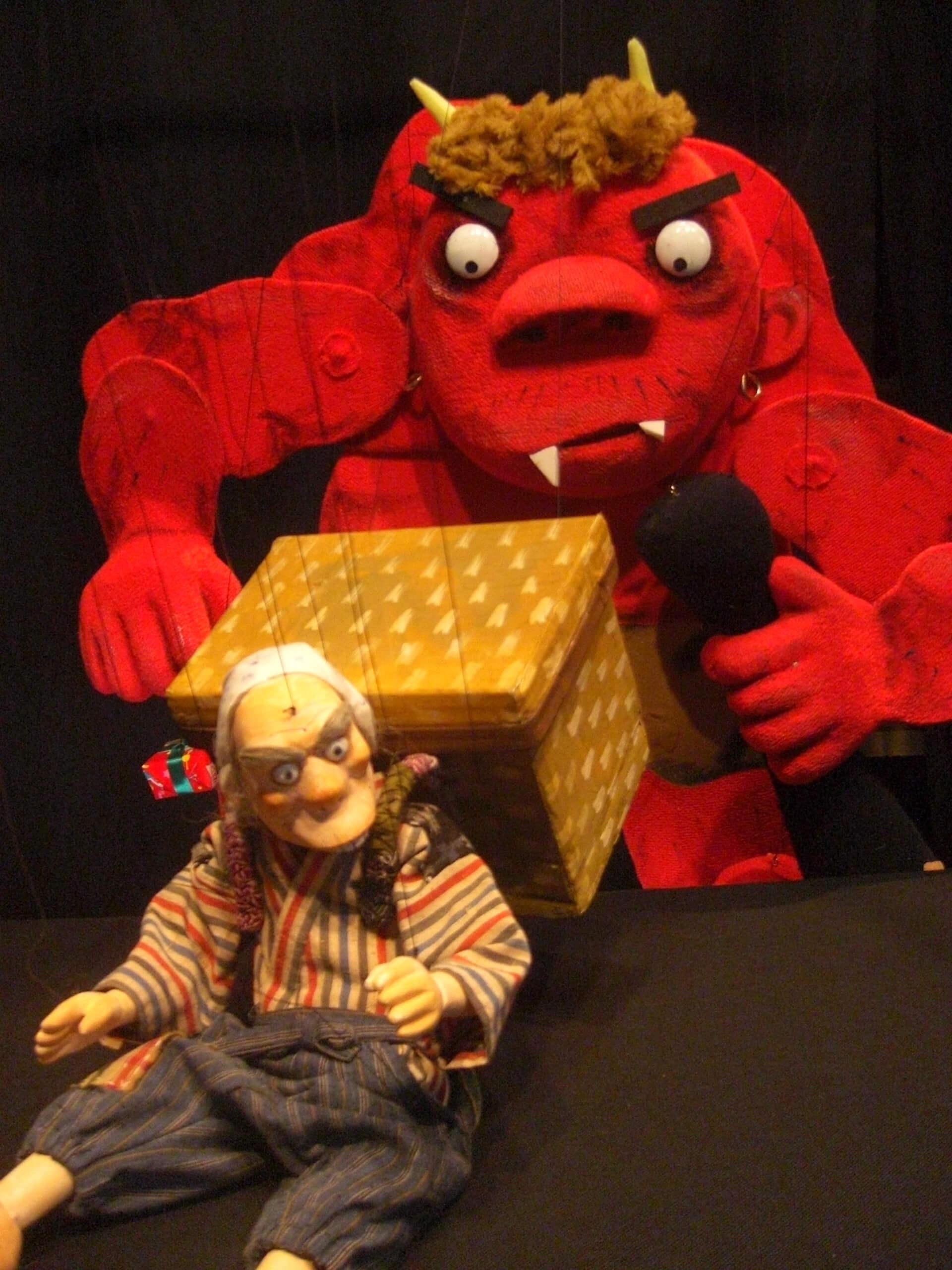 横浜人形の家 人形劇上演「舌切りスズメ」のメインビジュアル・赤鬼が襲っている写真
